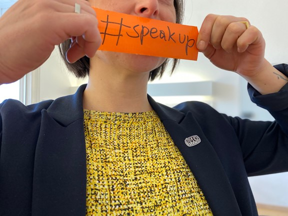 Person mit Hashtag-Plakat: Speakup